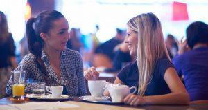 Mujer teniendo una comunicación efectiva en una cafetería con su amiga