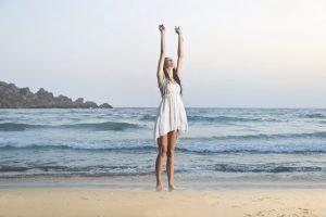 Mujer reduciendo el estrés en la playa vestida de blanco