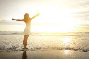 Be happy alone Smile Freedom and happiness woman on beach. She is enjoying serene ocean nature during travel holidays vacation outdoors. asian beauty
